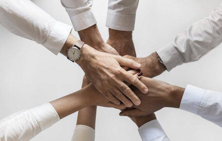 Mains qui se superposent pour montrer la cohésion d'équipe et le sentiment d'appartenance